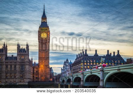 London England - The famous Big Ben and Houses of Parliament with iconic red double decker buses on Westminster Bridge at dusk