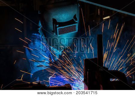 Industrial worker is welding in factory with protective mask