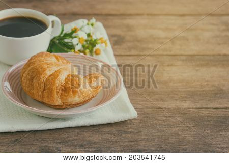 Homemade croissant on plate served with black coffee or americano. Delicious and quick breakfast with fresh croissant and coffee. Croissant and black coffee for breakfast on wood table with copy space. Coffee break with delicious croissant.