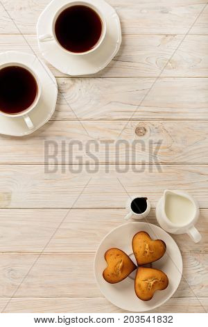 Cups with tea and cupcakes in the shape of a heart on a light wooden background. Top view.