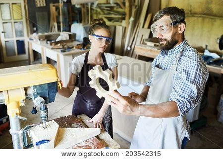 Group of hard-working carpenters looking at just finished wooden detail with concentration while standing at drill press machine, their aprons covered with sawdust