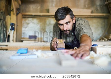 Concentrated bearded craftsman wearing apron smoothing plank with jointer plane, shavings scattered on table
