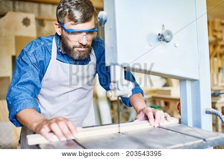 Middle-aged bearded craftsman wearing apron and safety goggles using sawing machine while working with wooden plank, blurred background
