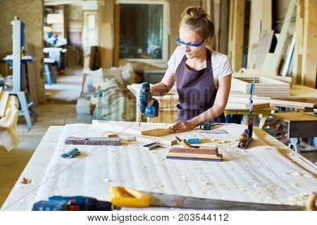 Attractive fair-haired carpenter in safety goggles and apron making holes in wooden detail with help of electric drill, interior of spacious workshop on background
