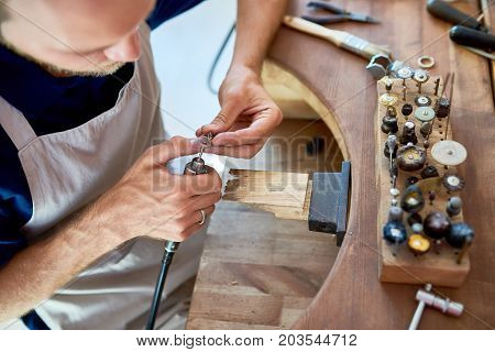 High angle portrait of jeweler making ring decoration in workshop, forming it on work station with different tools