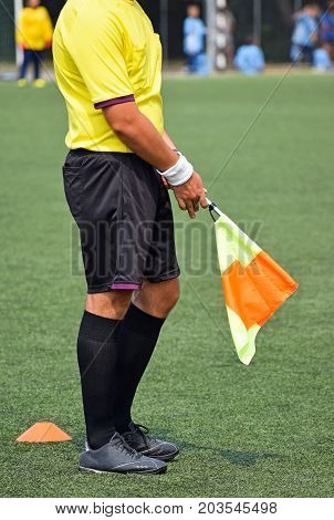 Soccer referee with a flag during the match