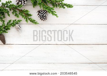 Christmas background. Fir tree branch and pine cones decoration rustic elements on white wooden. Creative flat lay top view design