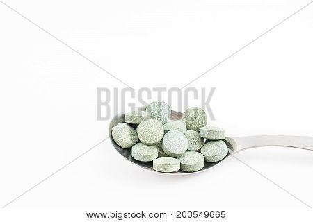 Spoon with Spirulina pills. Vitamin B12. White background.