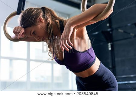 Portrait of tired young woman exhausted from training leaning on gymnastic rings during cross training workout in modern gym