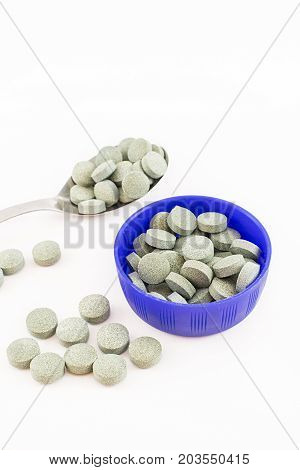 Container blue and spoon aluminiun with spirulina pills. White background. Vertical.