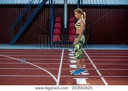 Portrait of a beautiful woman resting after run on stadium. Outdoor stadium