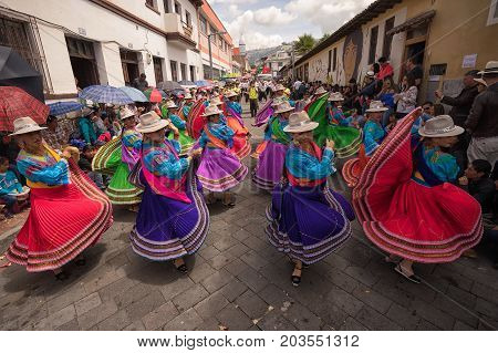 June 17 2017 Pujili Ecuador: indigenous women in brightly coloured clothing performing on the street during Corpus Christi parade