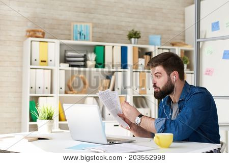 Portrait of agitated bearded man in casual wear using video call while working with laptop in modern office, discussing documentation via internet