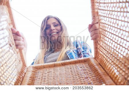 Portrait of happy young woman looking into wicker basket and smiling, shot from inside the box