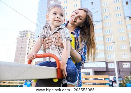 Portrait of young mother playing with little boy outdoors, swinging on modern playground in front of apartment building