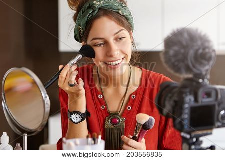 Camera Taking Photo Of Woman Putting Make Up On Her Face, Using Cosmetic Brushes. Beauty Blogger Wom