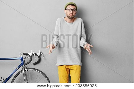 Young Male Student Wearing Fashionable Clothes, Standing Near Bicycle, Having Doubtful Expression Wh