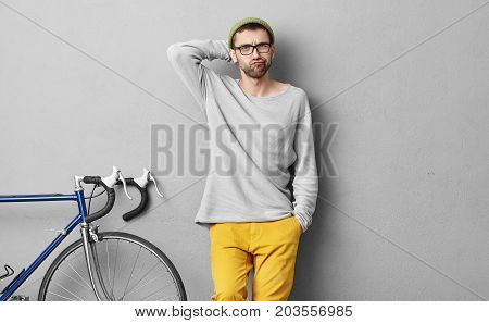 Portrait Of Fashionable Youngster Liking Active Lifestyle, Riding Bicycle Every Day, Having Unhappy