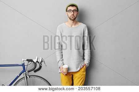 Hipster Male In Glasses, Trendy Clothes And Hat, Drinking Coffee Or Cappuccino, Being Upset To Notic