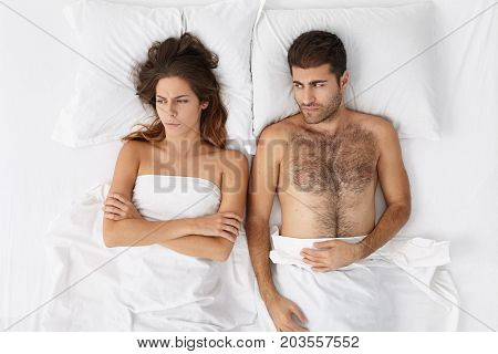Picture Of Upset Adult European Couple Having Marital Problems Or Disagreement Lying Side By Side In
