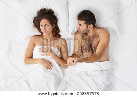 Top View Of Frustrated Young European Couple In Bed Having Fight. Mad Husband Interrogating His Unfa