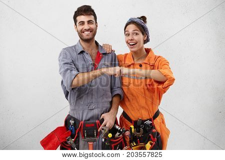 Successful Ecstatic Young Caucasian Man And Female Wearing Overalls And Carrying Working Instruments