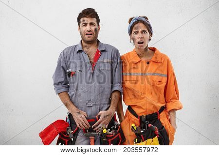 Picture Of Sad Disappointed Young Male And Female Plumbers Wearing Overalls And Carrying Equipment H
