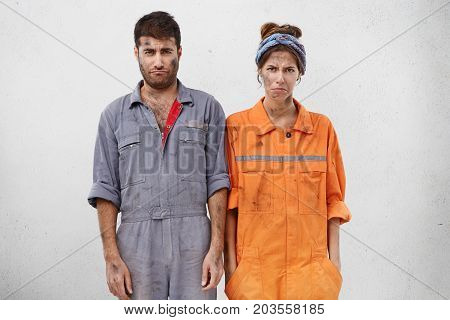 People, Manual Work And Tiredness Concept. Displeased Female And Male Technicians, Having Dirty Face
