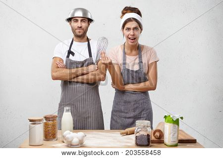 Discontent Female Cooking Supper, Wearing Apron, Standing At Kitchen With Her Husband Who Helps Her.