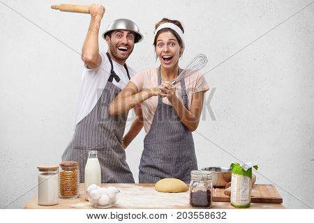 Funny Excited Couple Have Joy Together At Kitchen, Fight With Rolling Pin And Whisk, Foolish After H