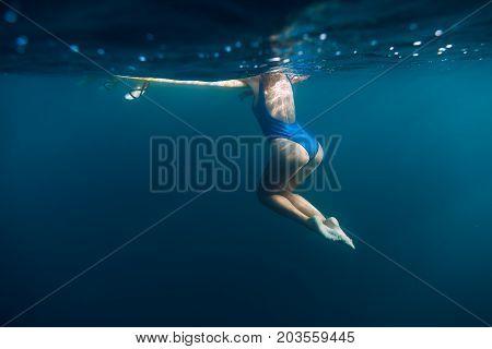 Underwater woman with blue bikini in ocean