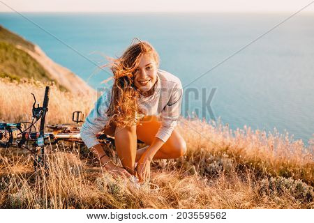 The smiled woman with bicycle on a walk tie her shoelaces