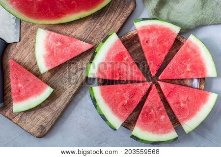 Slices of fresh seedless watermelon cut into triangle shape laying on a wooden plate flat lay horizontal