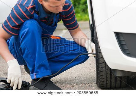 man pumping a tire car pump, close-up