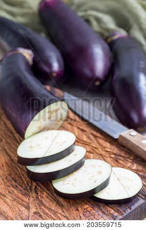 Preparing vegetable dish. Eggplant and eggplant slices on a wooden cutting board and background vertical