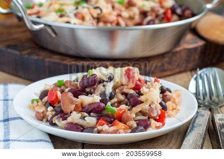 Baked casserole with different kinds of beans rice and cheese on white plate and in metal baking dish horizontal