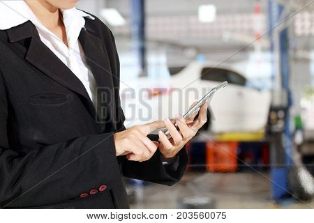 Businessmen and women are using mobile and touch smart phone and young female mechanic for mechanic inspecting on a car in auto repair shop