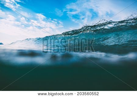 Crashing blue wave in ocean. Crystal wave and sun