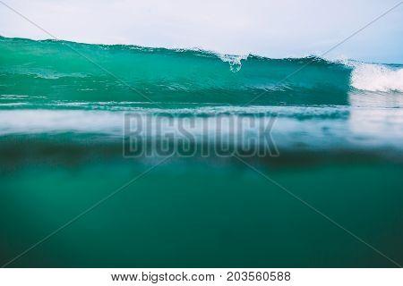 Crashing turquoise wave in Bali, Kuta beach. Crystal wave and sun