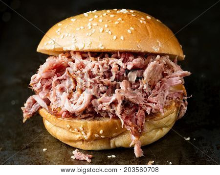 close up of rustic american barbecued pulled pork sandwich