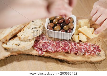 hands taking italian antipasti appetizers on table closeup