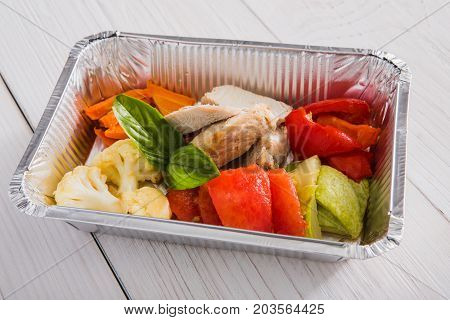 Business lunch at working place. Healthy food in office. Diet restaurant meals delivery in foil boxes: turkey with vegetables.