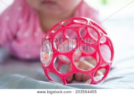 Close up newborn baby girl with pink suit while she is playing a pink ball on the bed. Focus on baby playing a pink ball.