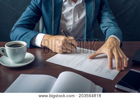 Businessman Signs Important Legal Documents On The Desktop With Cup Of Coffee