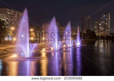 Large city luminous fountains on the river and the embankment