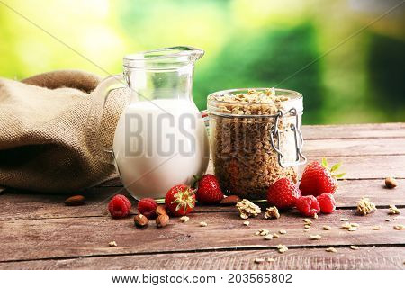 Healthy breakfast concept with oat flakes and fresh berries on rustic background. Food made of granola and musli. Healthy muesli with strawberries nuts and milk. poster