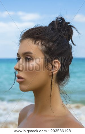 Close-up Portrait Of A Young Beautiful Well-groomed Girl In Profile On A Blue Sky And Sea Background