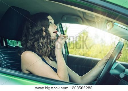 Driver Woman Looking In Mirror And Lipstick In Car. Distracted And Dangerous Driving. The Traffic Vi
