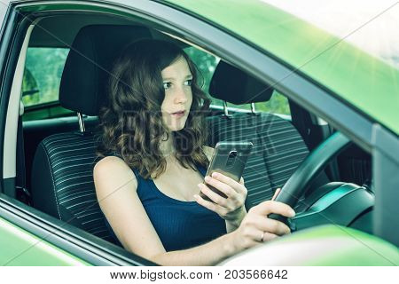 Driver Woman Looking At Phone In Car. Distracted And Dangerous Driving. The Traffic Violation.