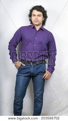 indian male model in purple check shirt and blue jeans